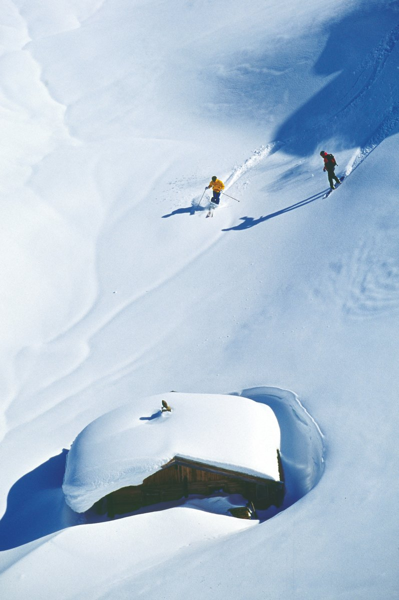 Snow Covered Alpine Hut And Skiers